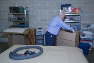 Arpin of RI packer in a basement packing the attachments of a shop vacuum into a carton so they are not misplaced during the move. F161