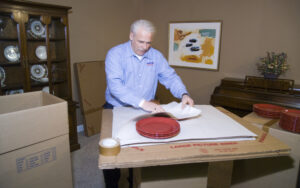 Arpin of RI packer in a dining room carefully wrapping fragile china plates with white newsprint.